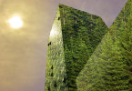 Green energy in the city: modern building covered with trees